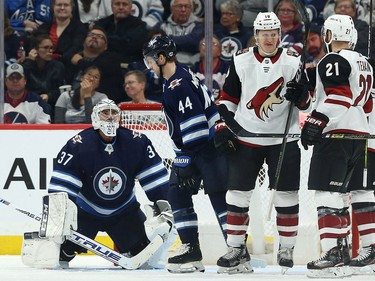 Winnipeg Jets goaltender Connor Hellebuyck (left) looks up at Josh Morrissey after a clearing attempt went into the Jets net during NHL action against the Phoenix Coyotes in Winnipeg on Tues., Oct. 15, 2019. Christian Dvorak (18) was credited with the goal. Kevin King/Winnipeg Sun/Postmedia Network ORG XMIT: POS1910152100598143
