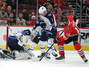 Winnipeg Jets goaltender Connor Hellebuyck (37) makes a save on a shot from Chicago Blackhawks centre Jonathan Toews (19) during the third period at the United Center. Dennis Wierzbicki-USA TODAY Sports