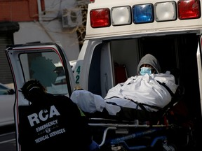 EMT's load a patient into an ambulance as health workers continued to test people for coronavirus disease (COVID-19) outside the Brooklyn Hospital Center in Brooklyn, New York City, March 27, 2020. (REUTERS/Andrew Kelly/File Photo)