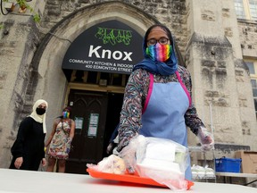 A volunteer places a meal on a table for pickup during a special Eid lunch service at Knox United Church in Winnipeg on Sun., May 24, 2020.