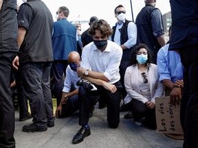 Prime Minister Justin Trudeau wears a mask as he takes a knee during a rally against the death in Minneapolis police custody of George Floyd, on Parliament Hill, in Ottawa, June 5, 2020.
