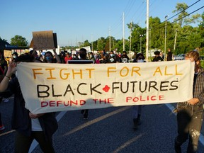 Protesters carry a banner calling to defund the police during a protest against police brutality in Florissant, Missouri, June 10, 2020.