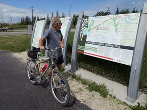 A cyclist consults a map for the Bishop Grandin Greenway Trail off Bishop Grandin Boulevard at River Road in the St. Vital area of Winnipeg on Tues., June 23, 2020. The city wants a committee to consider to consider historical markers. Kevin King/Winnipeg Sun/Postmedia Network