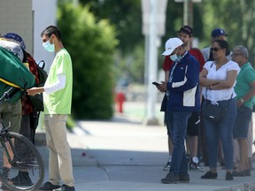 People wear masks while waiting to enter a bank in downtown Winnipeg on Friday.