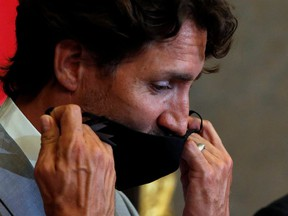 Canadian Prime Minister Justin Trudeau removes his mask on Parliament Hill on Aug. 18, 2020.