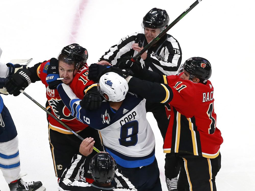 On ice officials try to break up a scuffle by Andrew Copp (9) of the Winnipeg Jets as he shoves Matthew Tkachuk (19) of the Calgary Flames as teammate Mikael Backlund (11) defends during a stop in play in the third period during Game Two of the Western Conference Qualification Round prior to the 2020 NHL Stanley Cup Playoffs at Rogers Place on August 3, 2020 in Edmonton, Alberta.