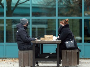 People wear masks and sit across a table outdoors at The Forks in Winnipeg on Sunday, Oct. 18, 2020.