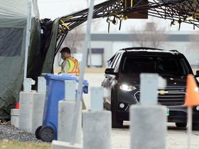A health care employee brings a sample inside at the drive-thru COVID-19 testing site in the parking lot of Red River College.