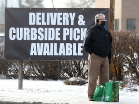 A person wears a mask while standing near a sign offering delivery and curbside pickup, in Winnipeg, during the Covid-19 pandemic..  Wednesday, November, 25/2020.Winnipeg Sun/Chris Procaylo/stf