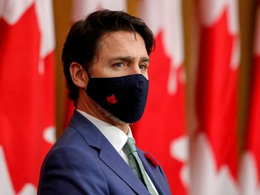 Prime Minister Justin Trudeau listens while wearing a mask at a news conference held to discuss the country's coronavirus response in Ottawa November 6, 2020.