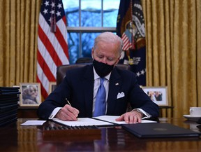 U.S. President Joe Biden sits in the Oval Office as he signs a series of orders at the White House in Washington, D.C., after being sworn in at the U.S. Capitol on Jan. 20, 2021.