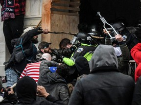 """Supporters of U.S. President Donald Trump battle with police at the west entrance of the Capitol building during a """"Stop the Steal"""" protest in Washington, D.C., Jan. 6, 2021."""