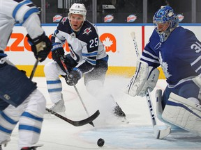 TORONTO, ON - JANUARY 18:  Paul Stastny #26 of the Winnipeg Jets feeds the puck in front of goalie Frederik Andersen #31 of the Toronto Maple Leafs during an NHL game at Scotiabank Arena on January 18. 2021 in Toronto, Ontario, Canada.