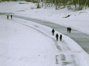 People enjoy mild weather by walking and skating along the Assiniboine River, in Winnipeg on Friday, Jan. 8.