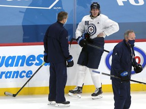 Patrik Laine grabs his side and grimaces in pain while speaking to head coach Paul Maurice before an early exit at Winnipeg Jets practice on Sunday, Jan. 17, 2021.