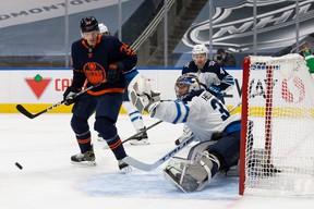 Jets goaltender Connor Hellebuyck makes a save on Alex Chiasson  of the Edmonton Oilers during Winnipeg's 3-2 loss at Rogers Place on Wednesday night.