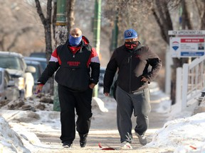 Two men with face coverings walk in the Osborne Village area of Winnipeg on Monday, Feb. 22, 2021.
