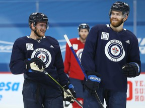 Andrew Copp (left) laughs with Adam Lowry during Winnipeg Jets practice at Bell MTS Place in Winnipeg on Tues., Feb. 23, 2021. Kevin King/Winnipeg Sun/Postmedia Network