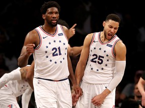 Joel Embiid (21) and Ben Simmons of the Philadelphia 76ers celebrate a win over the Brooklyn Nets at Barclays Center on April 20, 2019.