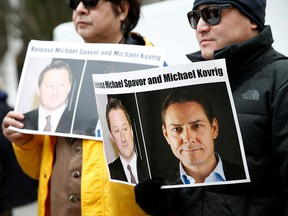 People hold signs calling for China to release Canadian detainees Michael Spavor and Michael Kovrig, in Vancouver March 6, 2019.
