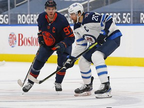 Winnipeg Jets forward Blake Wheeler (26) and Edmonton Oilers forward Connor McDavid (97) look for a loose puck during the third period  at Rogers Place in Edmonton on Saturday, March 20, 2021.