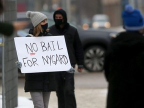 A group of people assembled near the law courts in Winnipeg to oppose a bail application made by lawyers representing Peter Nygard on Wednesday, Feb. 3, 2021.