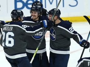 Winnipeg Jets forward Paul Stastny (right) celebrates his goal against the Vancouver Canucks in Winnipeg with Mark Scheifele (centre) and Blake Wheeler on Tuesday, March 2, 2021.