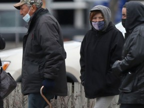 A group of people wear masks as they walk along a street, in Winnipeg on Friday, March 26, 2021.