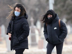 People crossing a street in strong winds, in Winnipeg on Tuesday.