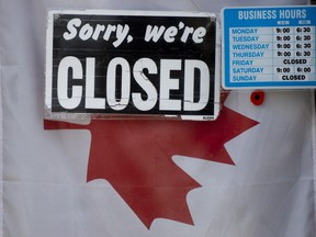 """A """"closed"""" sign hangs in a store window in Ottawa, Thursday April 16, 2020."""