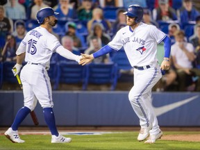 Toronto Blue Jays catcher Danny Jansen (right) celebrates with centre fielder Randal Grichuk after scoring against the Los Angeles Angels during the second inning at TD Ballpark on April 10, 2021.