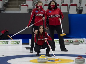 Team Canada skip Kerri Einarson of Gimli, Man., crouches in the rings as (back L-R), national team coaches Heather Nedohin and assistant national team coach Renee Sonnenberg during practice on April 29, 2021, before the start of the world women's curling championship in Calgary.