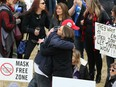 It was hugs over masks during an anti-mask rally at The Forks in Winnipeg on Sunday, April 25, 2021.