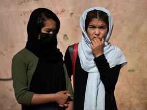 School girls stand near the site of yesterday's multiple blasts outside a girls' school in Dasht-e-Barchi on the outskirts of Kabul on May 9, 2021.
