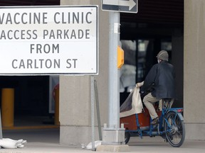 A person cycles by a sign at the COVID-19 vaccination supersite at RBC Convention Centre in Winnipeg on Tuesday, May 4, 2021.