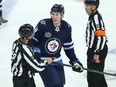 Winnipeg Jets defenceman Logan Stanley jaws with Edmonton Oilers forward Josh Archibald after his low hit in Game 3 of a Stanley Cup playoff series in Winnipeg on Sunday, May 23, 2021.