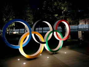 The Olympic rings are illuminated in front of the National Stadium in Tokyo, Jan. 22, 2021.