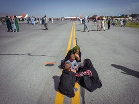 Afghan people sit along the tarmac as they wait to leave the Kabul airport in Kabul on August 16, 2021.