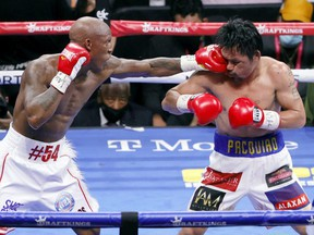Yordenis Ugas (left) hits Manny Pacquiao in the sixth round of their WBA welterweight title fight at T-Mobile Arena in Las Vegas, Saturday, Aug. 21, 2021.