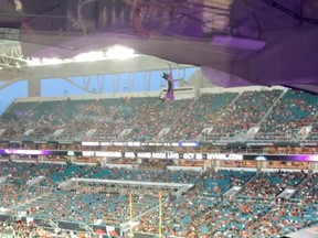A cat hangs on an upper deck of the Hard Rock Stadium before losing grip, in Miami Gardens, Florida, Sept. 11, 2021, in this still image obtained from social media video.