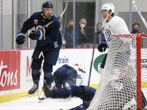 Brenden Dillon (left) draws a reaction from Adam Lowry (right) after his hit on Kristian Vesalainen also knocked down Ville Heinola during the first day of Winnipeg Jets training camp in Winnipeg on Sept. 23, 2021.