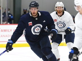 Pierre-Luc Dubois (left) chases the puck during the first day of Winnipeg Jets training camp on Thursday.