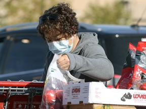 A woman wearing a mask loads groceries in south Winnipeg on Monday, Sept. 27, 2021.