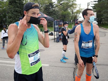 Manitoba Marathon winner Brian Walker (left) masks up in the finish area on Chancellor Matheson in Winnipeg with second-place finisher Tom Sherwin on Sunday, Sept. 5, 2021.