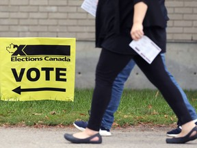 People have their voter cards ready as they head toward a polling station at Centre Culturel Franco-Manitobain in Winnipeg on Mon., Sept. 20, 2021.