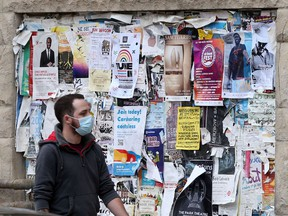 A person wears a mask while walking past posters on a wall, in Winnipeg on Thursday, September 22, 2021.