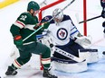 Connor Hellebuyck  of the Winnipeg Jets makes a save as Kevin Fiala of the Minnesota Wild looks for the rebound in the third period at Xcel Energy Center on Tuesday.