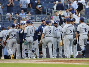 The Tampa Bay Rays celebrate after defeating the New York Yankees 12-2 at Yankee Stadium at Yankee Stadium in New York on Oct. 2, 2021. The Rays' victory was the team's 100th of the season.