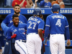Vladimir Guerrero Jr. of the Toronto Blue Jays celebrates with Teoscar Hernnadez after hitting a two-run home run against the Baltimore Orioles at Rogers Centre on October 2, 2021 in Toronto.