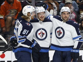 ANAHEIM, CALIFORNIA - OCTOBER 26: Dylan DeMelo #2 and Kyle Connor #81 congratulate Evgeny Svechnikov #71 of the Winnipeg Jets after his goal during the second period of a game against the Anaheim Ducks at Honda Center on October 26, 2021 in Anaheim, California.